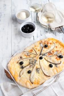 Pizza mit briekäse und aubergine auf einem weißen hölzernen hintergrund.