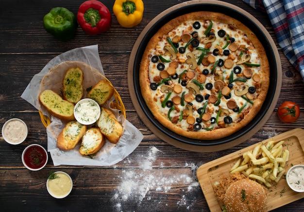 Pizza mit burger, knoblauchbrot auf holztisch, draufsicht