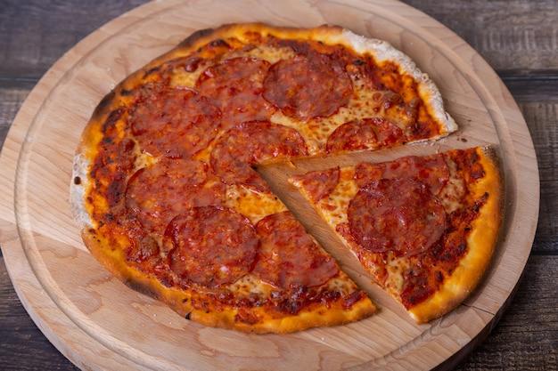 Pizza mit chorizo-wurst auf einem holzbrett. ganze pizza, ein stück abgeschnitten. nahansicht.