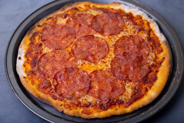 Pizza mit chorizo-wurst auf einem schwarzen hintergrund. ganze pizza. nahansicht.