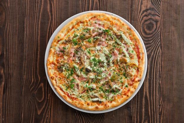 Pizza mit dünner kruste, schinken, kürbis und austernpilzen
