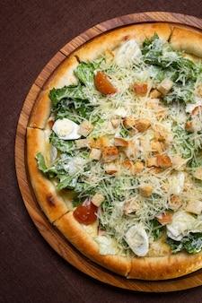 Pizza mit ei und grünem vegetarischem salat.