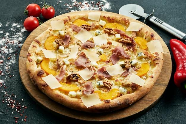 Pizza mit einer großen anzahl von belägen: jamon, parmesan, nüsse, blauschimmelkäse und pfirsiche. pizza in komposition mit zutaten auf einem schwarzen tisch