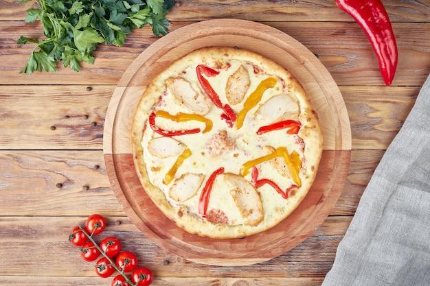 Pizza mit fleisch, gemüse und pilzen, hölzerner hintergrund