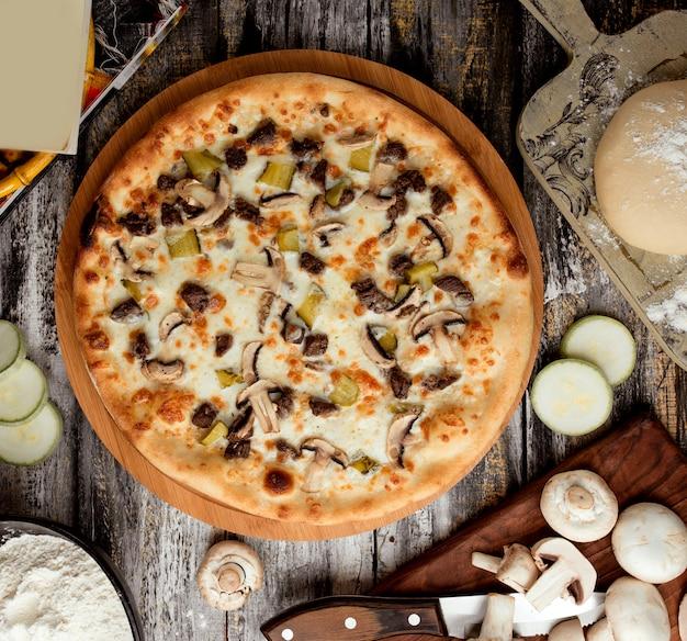 Pizza mit fleisch und pilzen