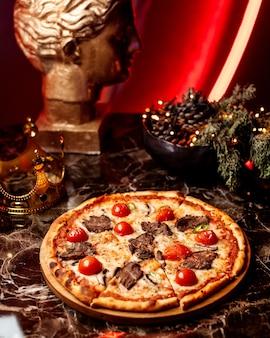 Pizza mit fleischstücken und tomaten