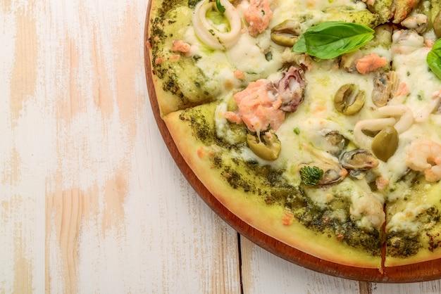 Pizza mit garnelen, lachs und oliven, pesto
