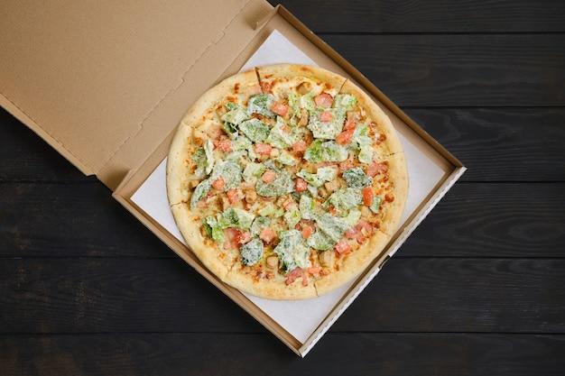 Pizza mit gebratenem hühnerfleisch, salat und tomate auf dunklem holztisch in kartonverpackung