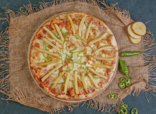 Pizza mit gebratenen kartoffelstöcken, tomate und grünem paprika