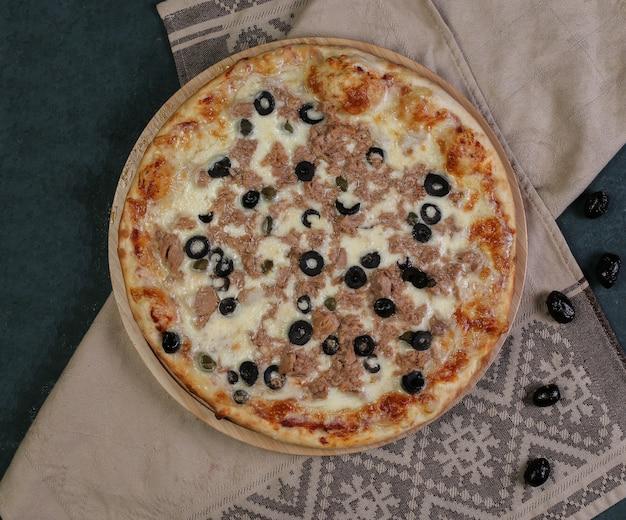 Pizza mit gehacktem fleisch und schwarzen oliven