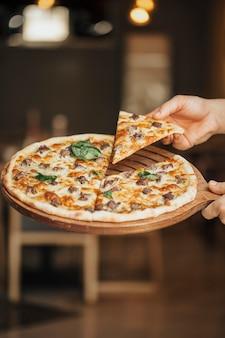 Pizza mit gemischten zutaten auf einem holzbrett, eine scheibe nehmend