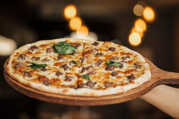 Pizza mit gemischten zutaten auf einem holzbrett