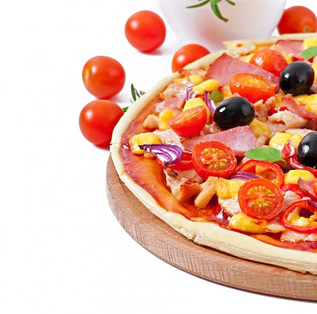 Pizza mit gemüse, huhn, schinken und oliven isoliert auf weiß