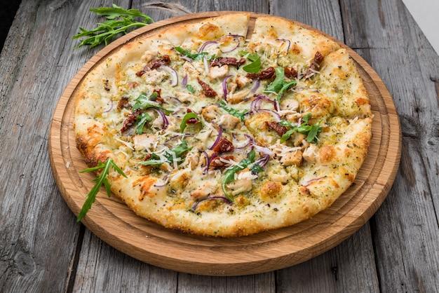 Pizza mit getrockneten tomaten, schinken, rucola und parmesan