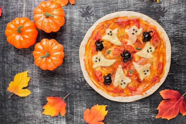 Pizza mit gruseligen geistern an der spitze und kürbisse