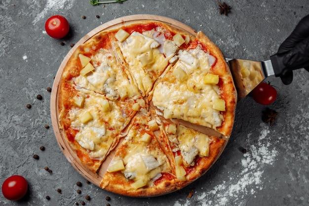 Pizza mit hähnchenbrust, ananas und mozzarella