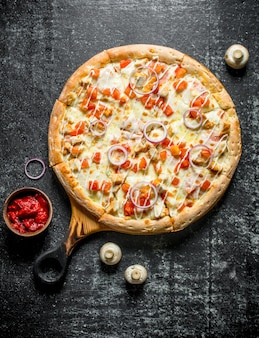 Pizza mit hühnchen-käse-sauce. auf dunkler rustikaler oberfläche