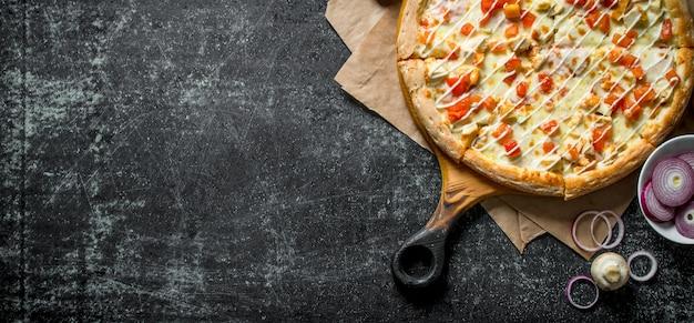 Pizza mit hühnchen-käse-sauce auf schwarzem holztisch