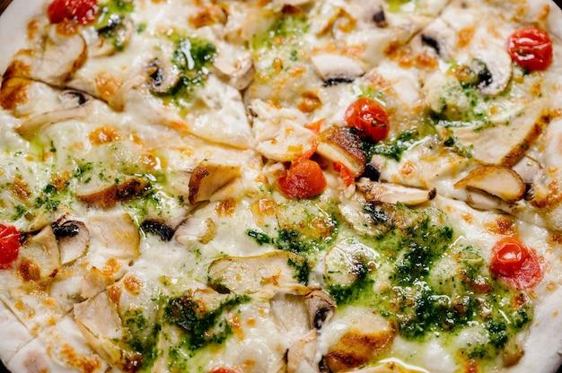 Pizza mit hühnchen, mozzarella, oliven und basilikum draufsicht mit kopierraum