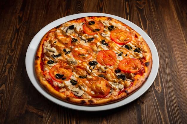Pizza mit hühnerfleisch, pilzen, tomaten und schwarzen oliven, holzhintergrund, zurückhaltend
