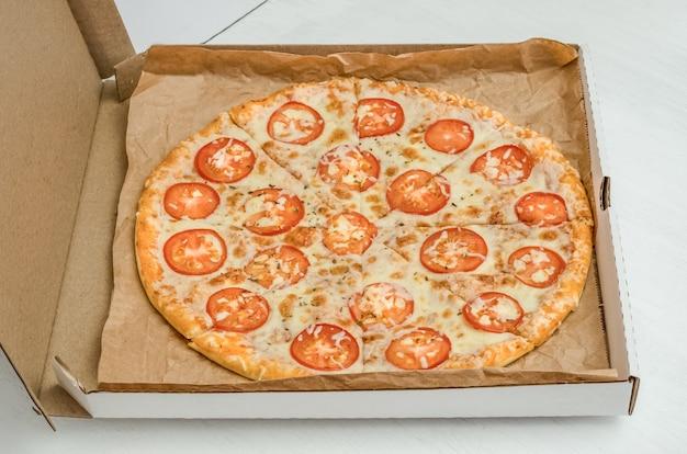 Pizza mit käse und tomaten auf einer weißen hölzernen hintergrundnahaufnahme.