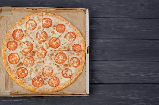 Pizza mit käse und tomaten in einer box mit kopienraum auf einem dunklen hölzernen hintergrund.