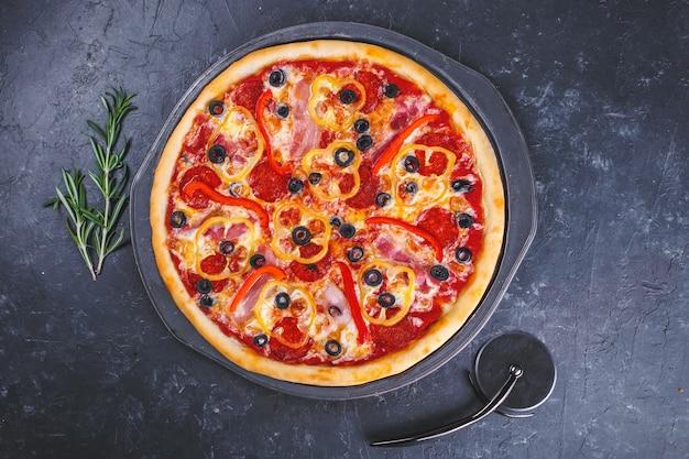Pizza mit käsefleischpfeffern und -tomaten auf dunkelheit