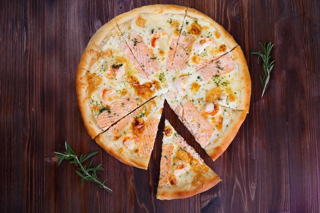 Pizza mit käsefleischpfeffern und -tomaten auf holz