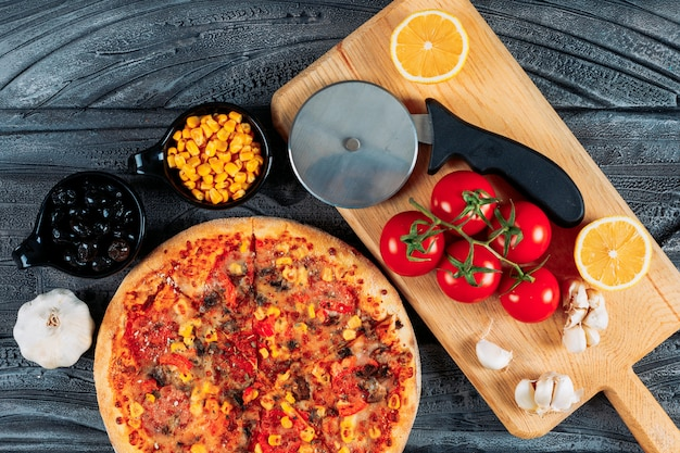 Pizza mit knoblauch, tomaten, einer zitrone, oliven, mais und einer pizzaschneider-draufsicht auf einem dunklen hölzernen hintergrund