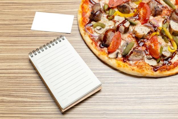 Pizza mit leerem papier mit kopie copyspace