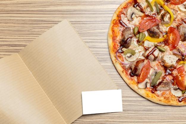 Pizza mit leerem papier mit kopienraum