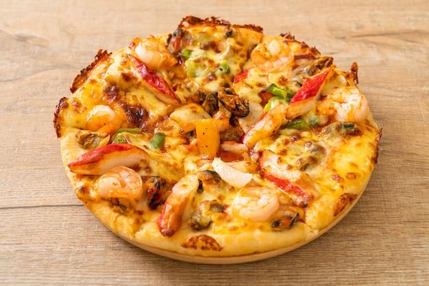 Pizza mit meeresfrüchten (garnelen, tintenfisch, muschel und krabben) auf einem holztablett