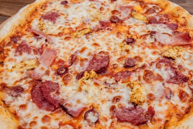 Pizza mit mozzarella, salami, tomaten, pfeffer, gewürzen. italienische pizza