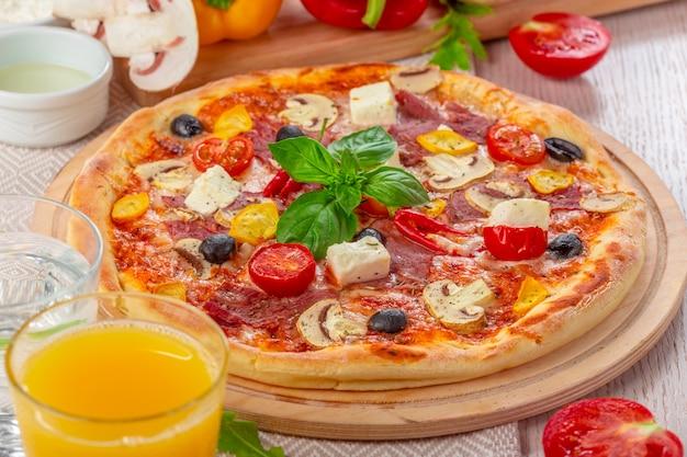 Pizza mit mozzarella, schinken, cherry tomatoes, schwarzen oliven