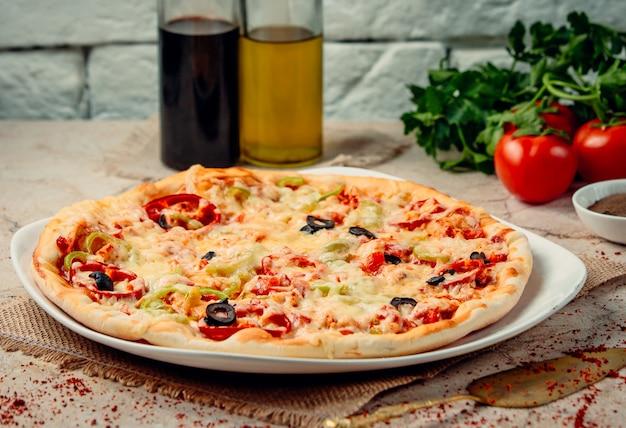 Pizza mit paprika auf dem tisch