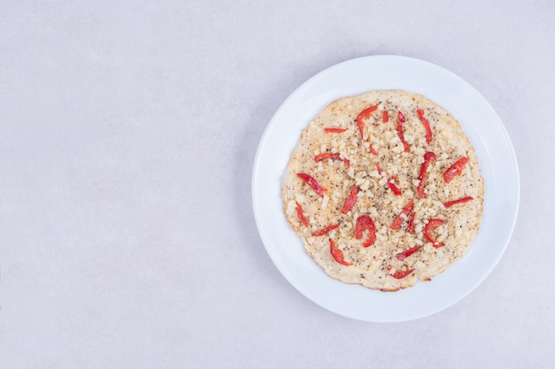 Pizza mit paprika auf holzteller auf weiß