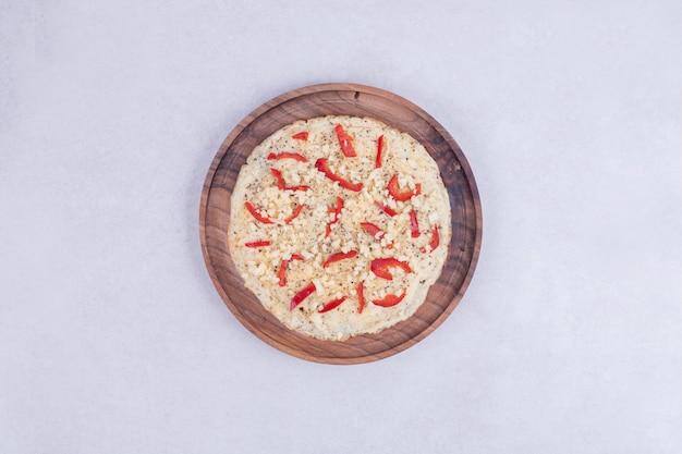 Pizza mit paprika auf holzteller