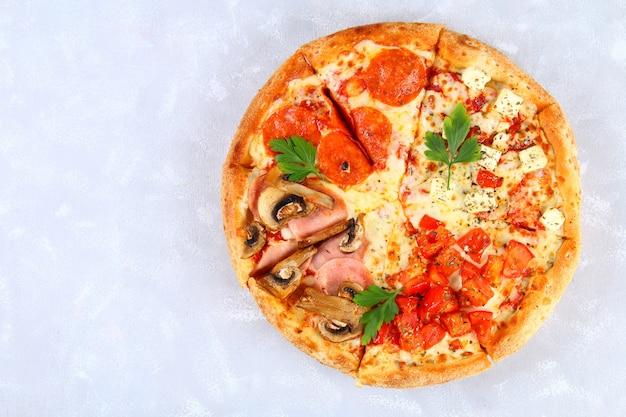 Pizza mit peperoni, champignons, tomaten und käse. vier geschmäcker in einer pizza. grauer konkreter tisch.