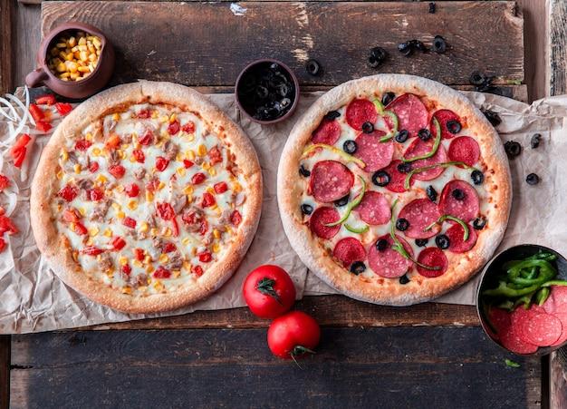 Pizza mit peperoni und hähnchen mit gemischtem gemüse