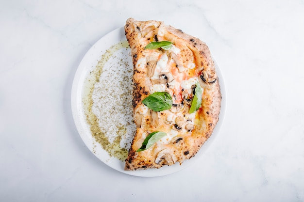 Pizza mit pilz-, mozarella- und basilikumblättern.