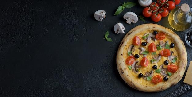 Pizza mit pilzen, tomaten und oliven auf einem dunklen hintergrund