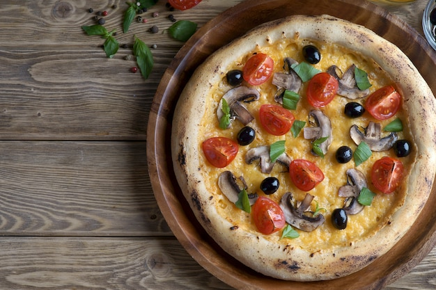 Pizza mit pilzen, tomaten und oliven auf einem hölzernen hintergrund