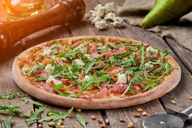 Pizza mit prosciutto birne blauschimmelkäse pinienkerne und rucola