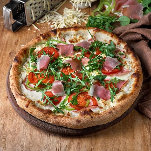 Pizza mit prosciutto parmaschinken, rucolasalat auf holzhintergrund.