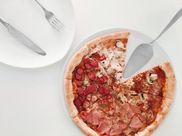 Pizza mit roten tomaten, mozzarella auf einem weißen tisch