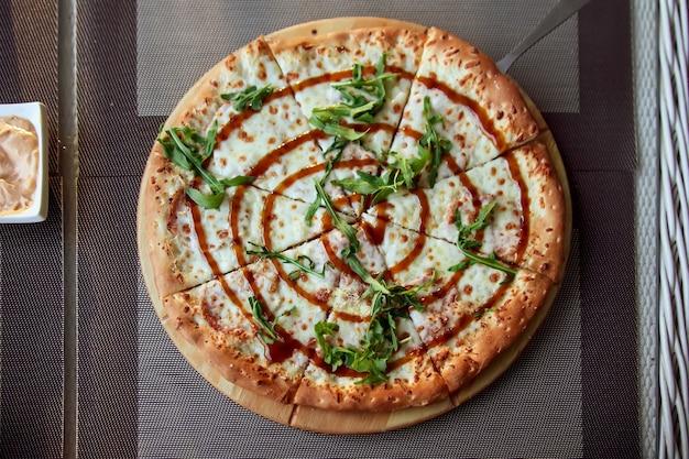 Pizza mit rucola auf einer holzplatte auf grauem hintergrund auf der sommerterrasse.