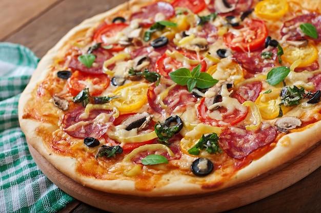 Pizza mit salami, tomate, käse und oliven