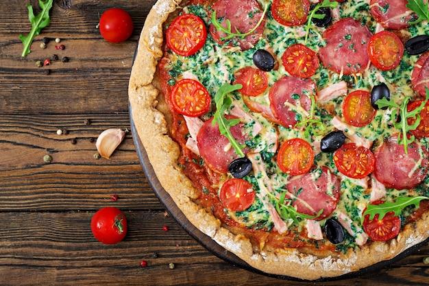 Pizza mit salami, tomaten, oliven und käse auf einem teig mit vollkornmehl. italienisches essen. draufsicht. flach liegen.