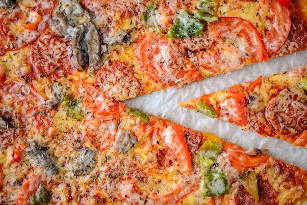 Pizza mit salami, tomaten, pfeffer und pilzen ist die draufsicht. nahansicht