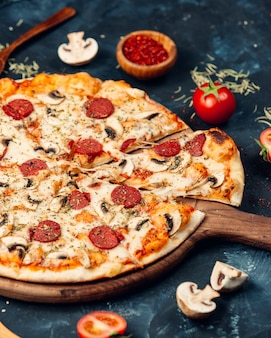 Pizza mit salami und pilzen